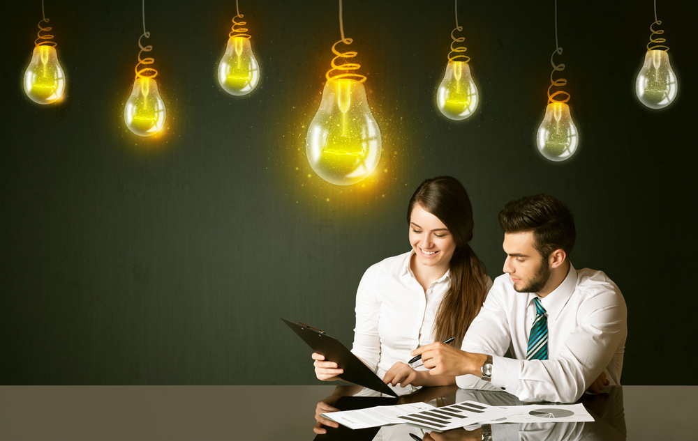 People sitting at the black table with idea bulbs on the background